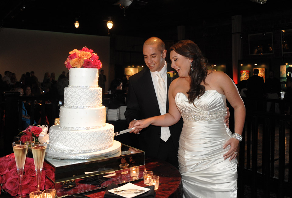 Bride and groom are cutting the cake by More than Cakes at Gallery M squared