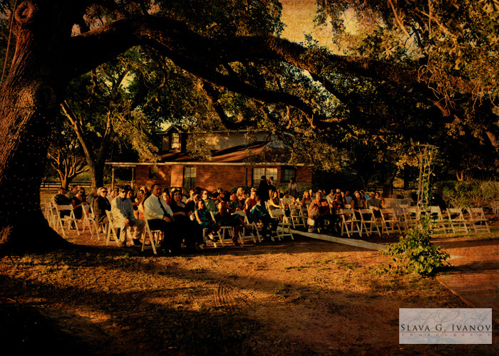wedding ceremony outside under a big oak tree at oakland farm and ranch in Tomball Tx