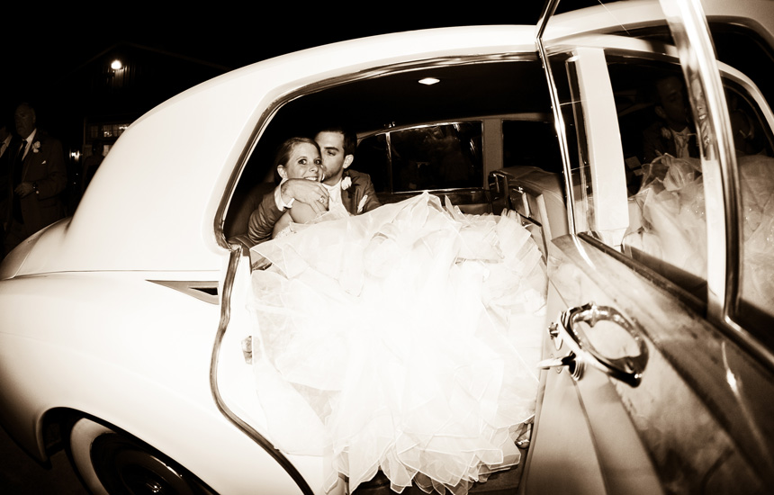 Newlywed couple inside a get away car leaving Ashelynn Manor after the wedding