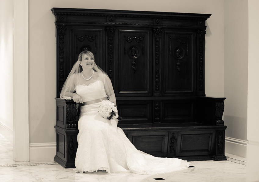 Bride posing for photographer before her wedding in the lobby of the Tremont House Hotel