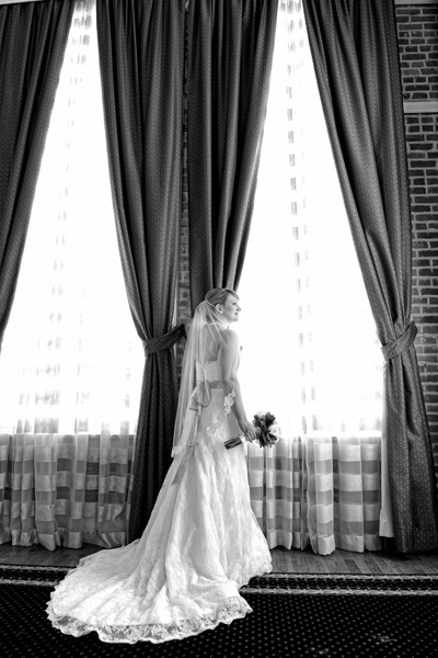 Bride looking out of the window at the Tremont House Hotel Galveston, Texas