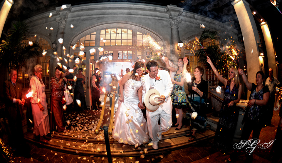 Newlywed couple leaving their reception with guests holding sparklers.