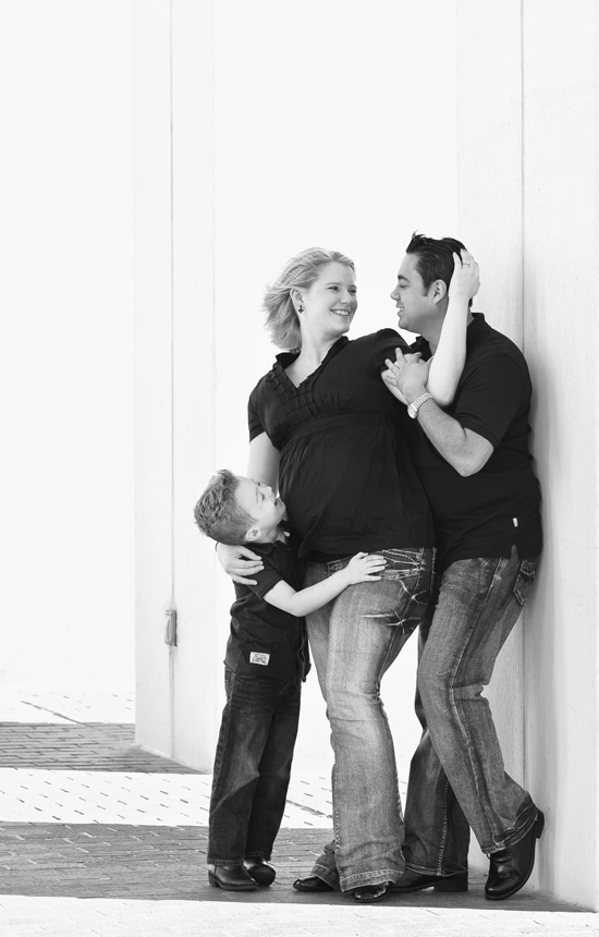 Mother, father and child posting in front of the camera during their maternity  photo session family style